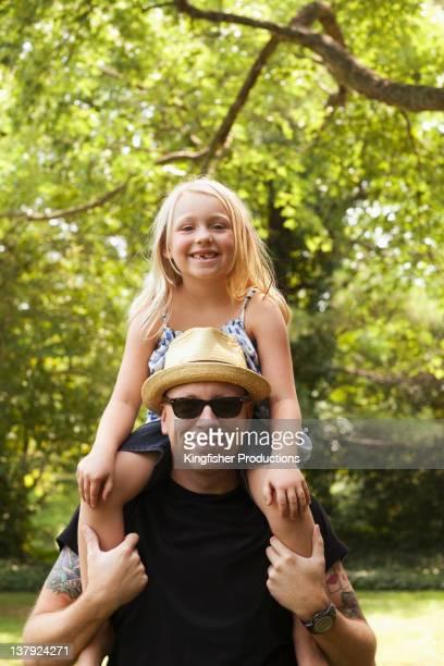 Caucasian man carrying daughter on shoulders