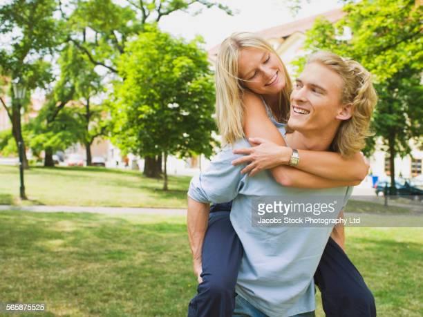 Caucasian man carrying girlfriend piggyback in park