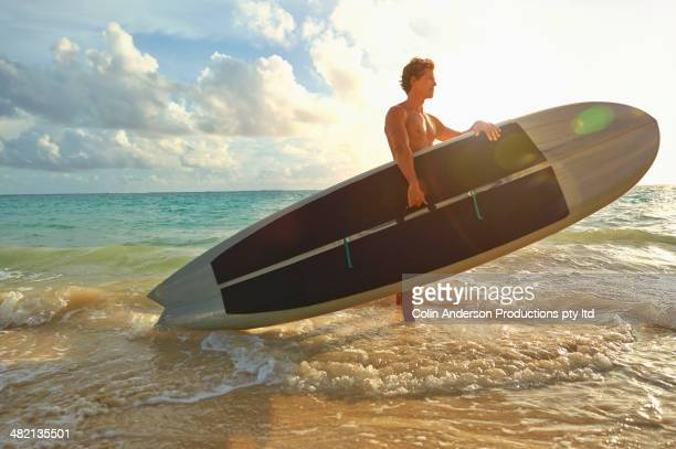 Caucasian man carrying paddle board in ocean surf