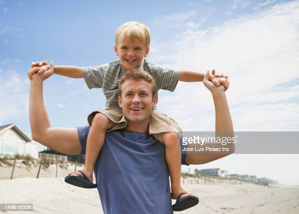 Caucasian man carrying son on shoulders at beach
