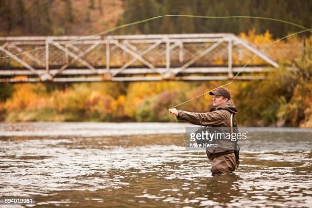 Caucasian man casting in river