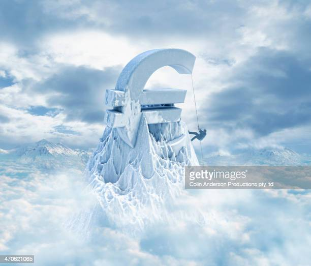 Caucasian man climbing Euro sign on snowy mountaintop