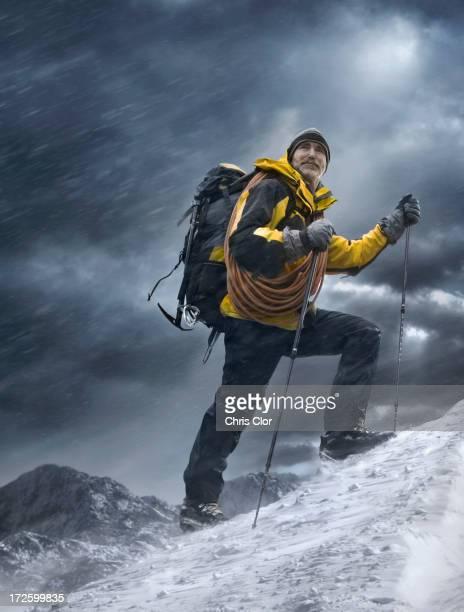 Caucasian man climbing snowy mountain
