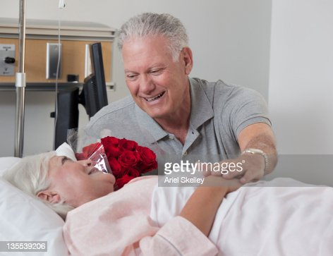 Caucasian man comforting wife in hospital : Stock Photo