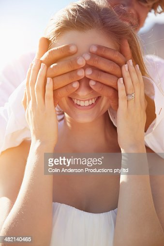 Caucasian man covering girlfriend's eyes