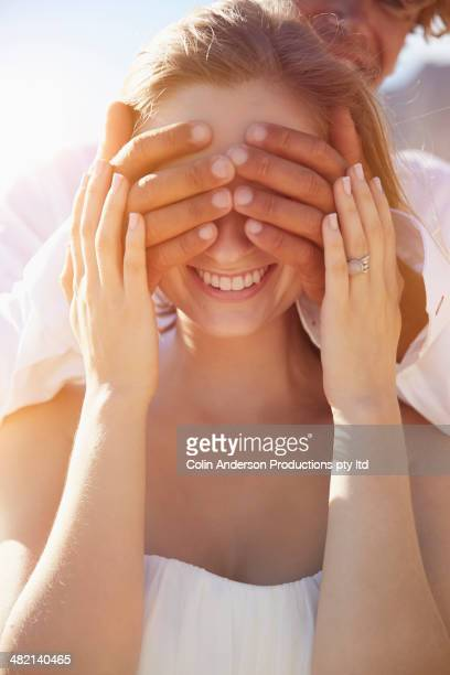 Caucasian man covering girlfriend's eyes
