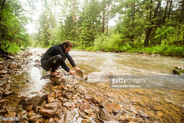 Caucasian man crouching in forest river