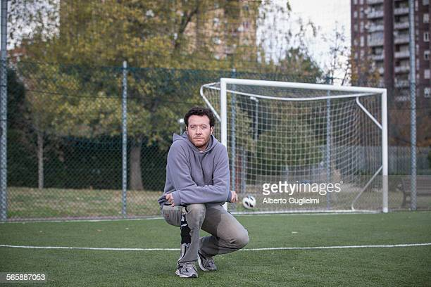 Caucasian man crouching on soccer field in urban park