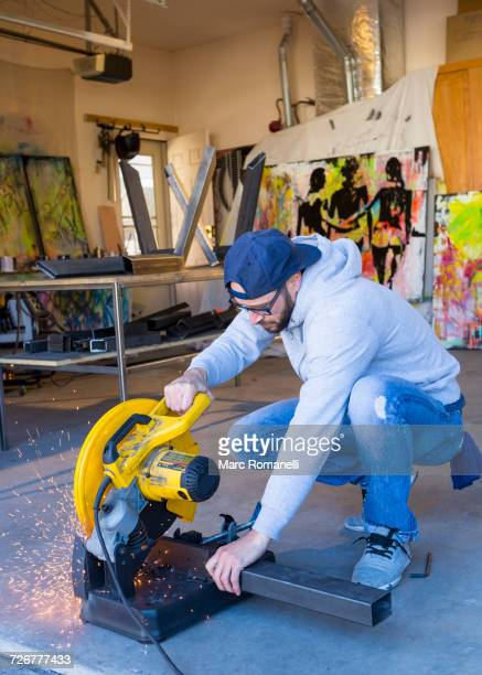 Caucasian man cutting metal with saw