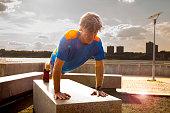 Caucasian man doing push ups in urban park