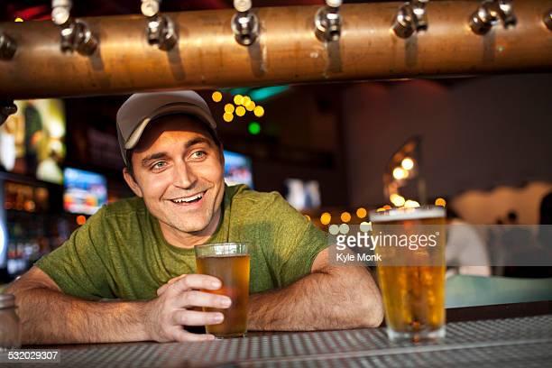 Caucasian man drinking beer in bar
