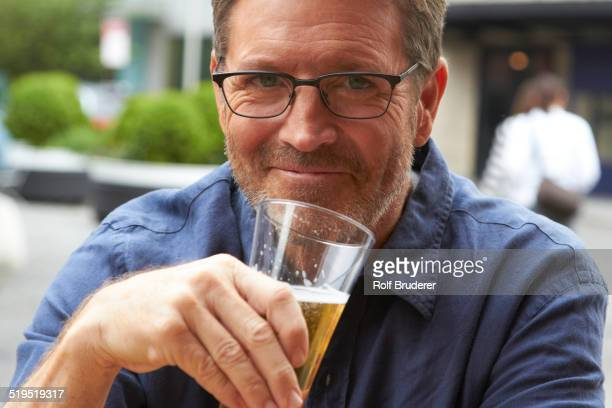 Caucasian man drinking beer outdoors