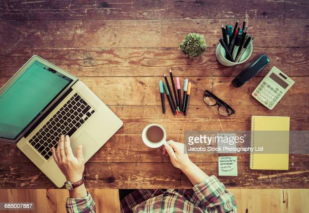 Caucasian man drinking coffee and using laptop at wooden table