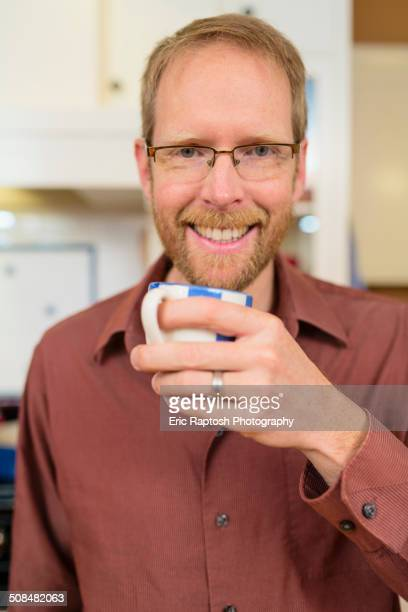 Caucasian man drinking cup of coffee in kitchen