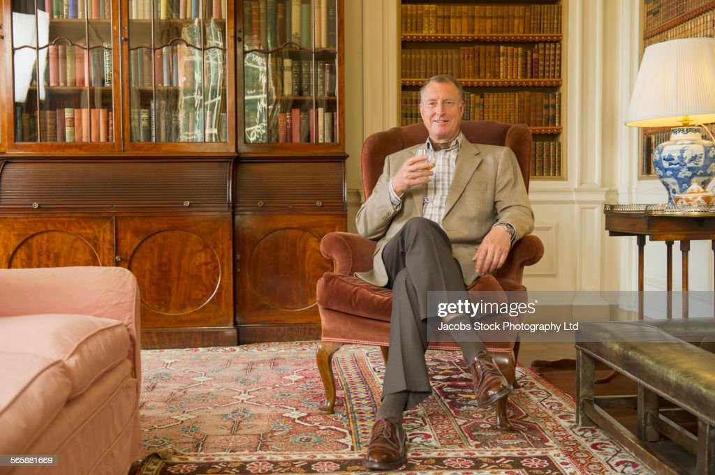 Caucasian man drinking in ornate library : Stockfoto