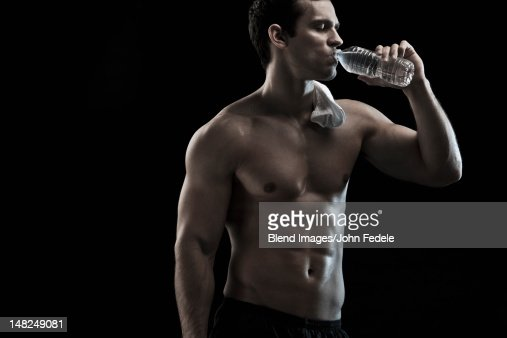 Caucasian man drinking water after exercise : Stock Photo