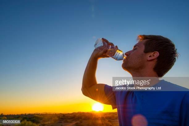 Caucasian man drinking water bottle in remote field