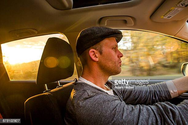 Caucasian man driving car at sunset