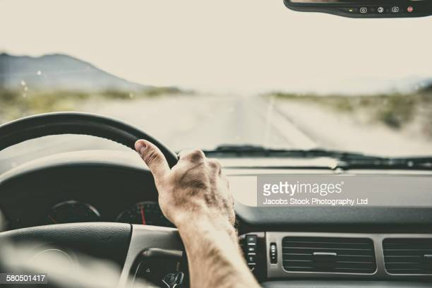 Caucasian man driving car on remote road