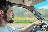 Caucasian man driving car on rural road