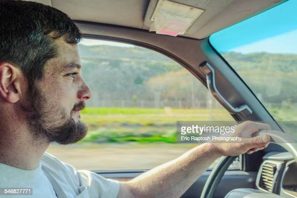 Caucasian man driving car on rural road