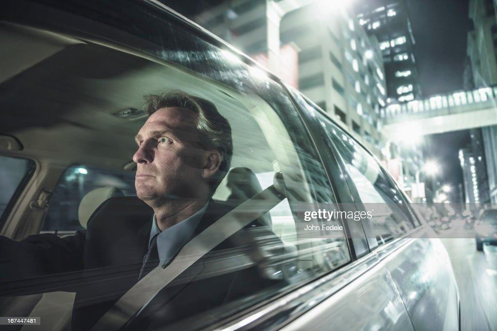 Caucasian man driving on city street : Stock Photo