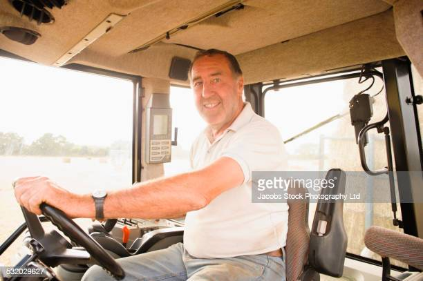 Caucasian man driving tractor outdoors
