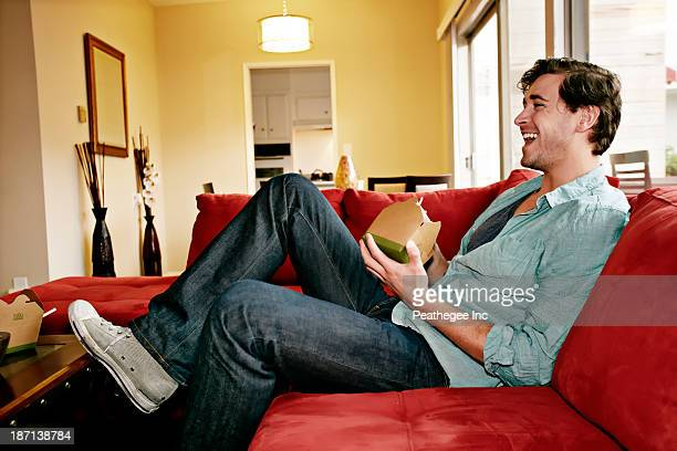 Caucasian man eating take out food on sofa