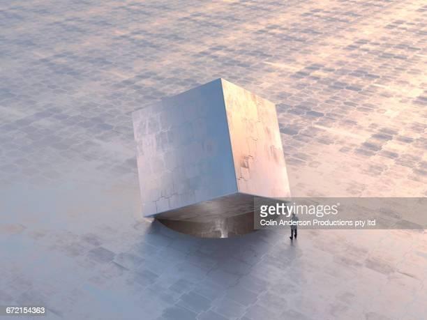 Caucasian man examining square metal box in round hole
