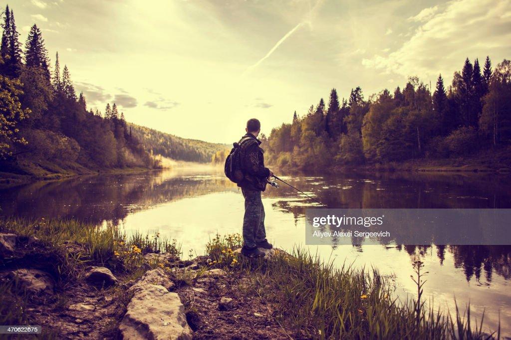 Caucasian man fishing at lakeside