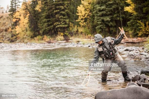 Caucasian man fishing in river holding net