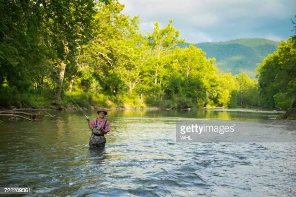 Caucasian man fishing in river