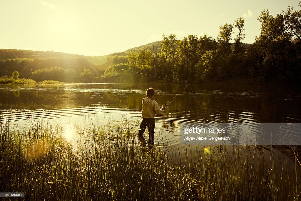 Caucasian man fishing in still lake