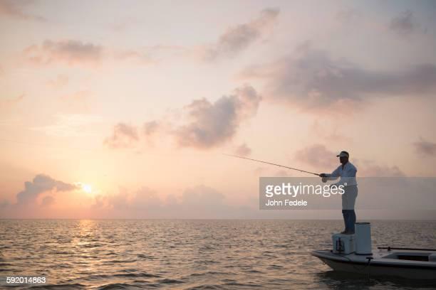 Caucasian man fishing on boat in ocean