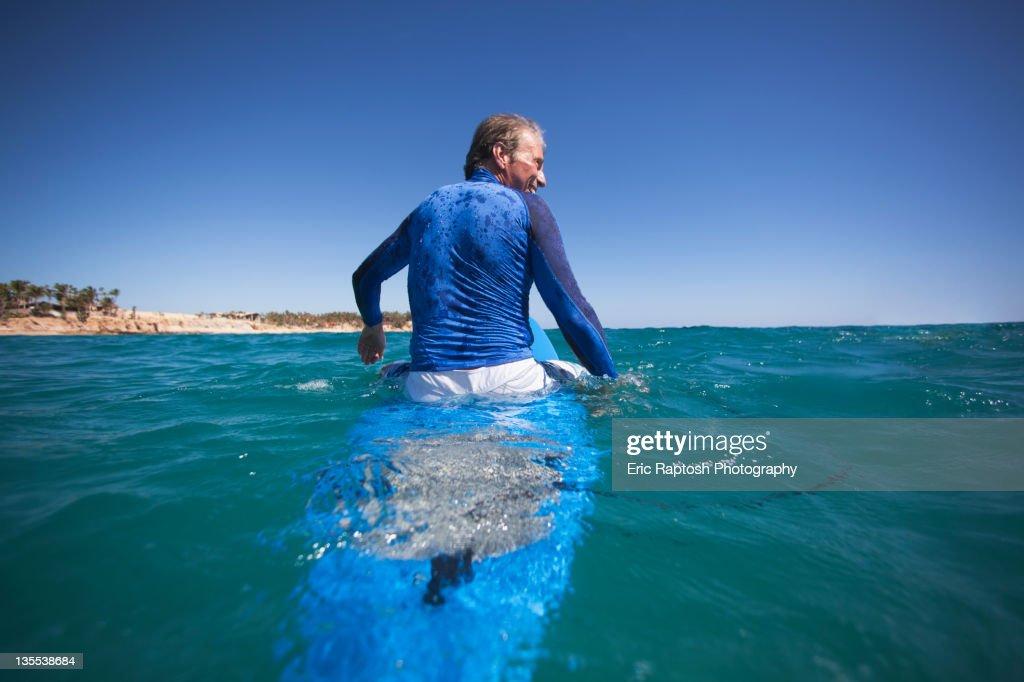 Caucasian man floating on surfboard : Stock Photo