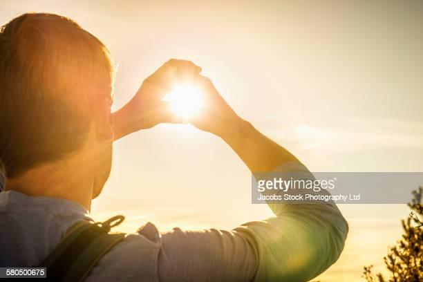 Caucasian man framing hands around sun