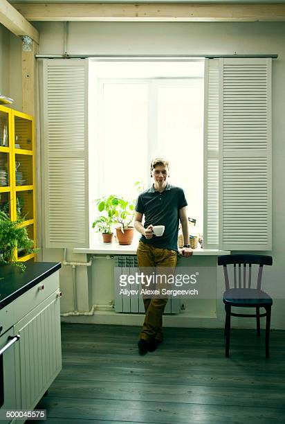 Caucasian man having coffee in kitchen