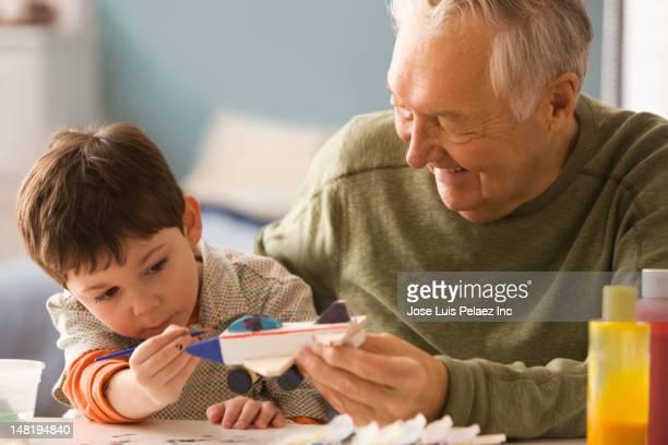 Caucasian man helping grandson paint toy airplane