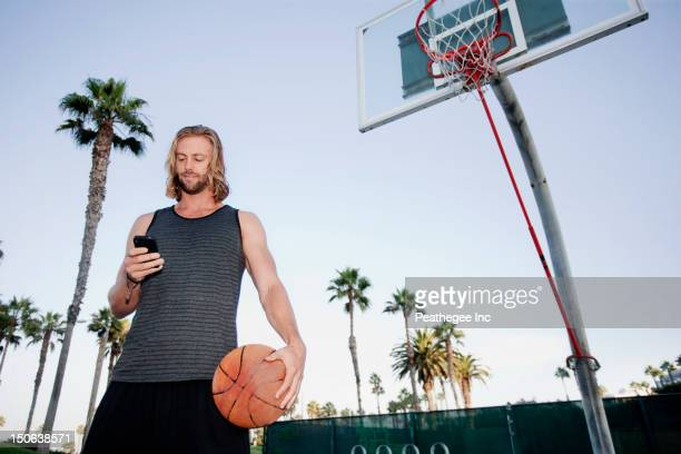 Caucasian man holding basketball and text messaging on cell phone