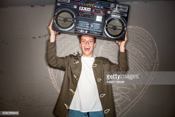 Caucasian man holding boom box near chalk heart on wall