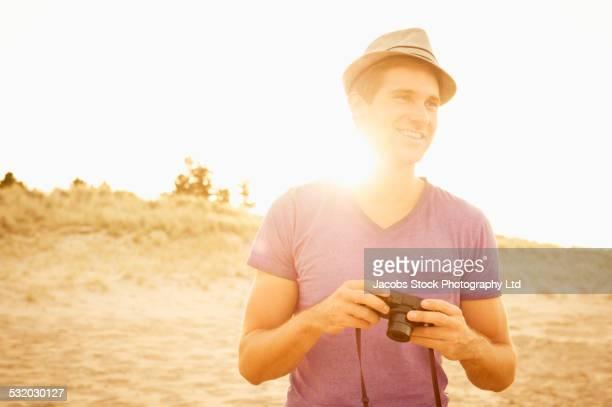 Caucasian man holding camera on beach