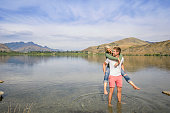 Caucasian man holding girlfriend in rural lake