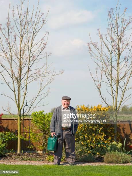 Caucasian man holding watering can in backyard garden