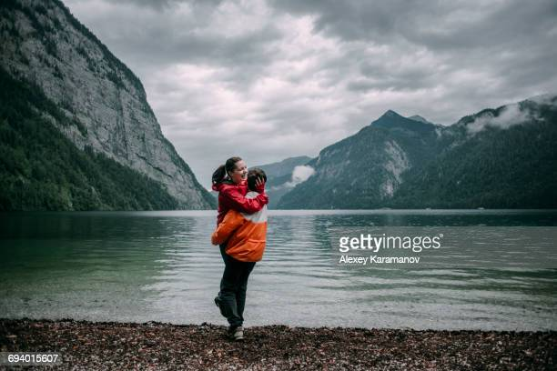 Caucasian man hugging near mountain lake