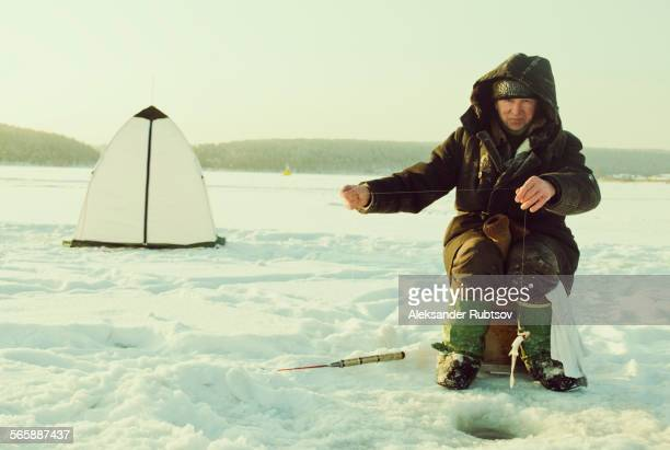 Caucasian man ice fishing on remote lake