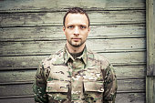 Young serious Caucasian military man in camouflage uniform. Frontal portrait over green wooden wall