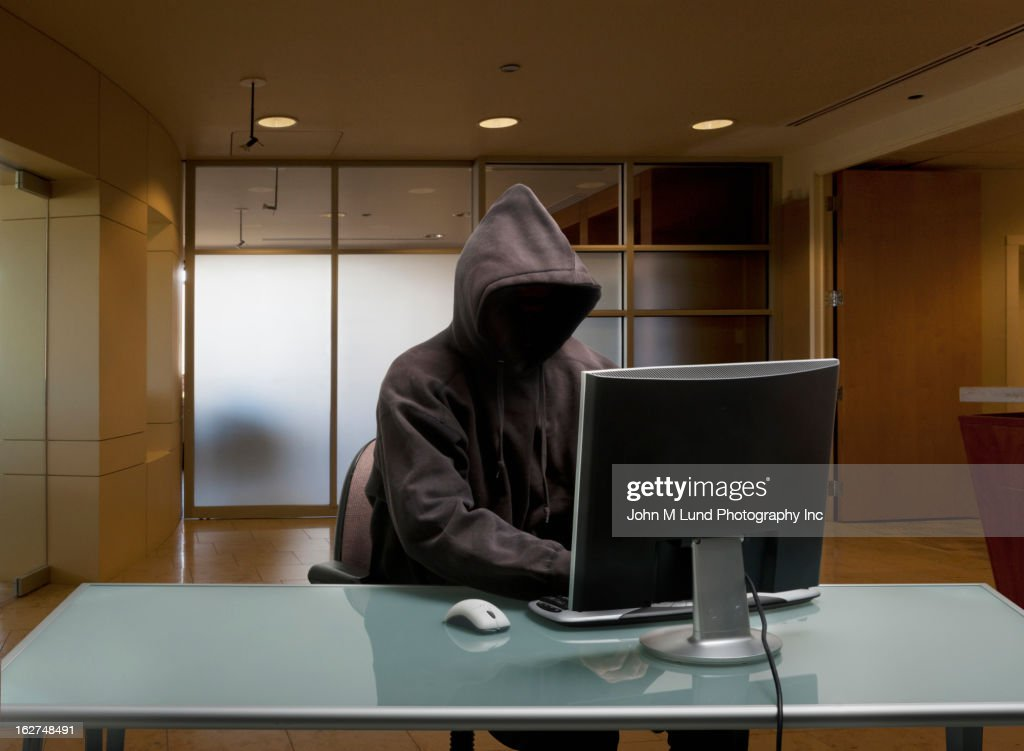Caucasian man in hoody sitting at office desk : Stock Photo