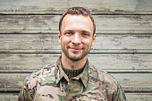 Young smiling Caucasian man in military camouflage uniform. Outdoor closeup portrait over green rural wooden wall