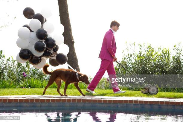 Caucasian man in pink suit mowing lawn being followed by dog