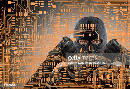 Caucasian man in ski mask behind microchip pattern